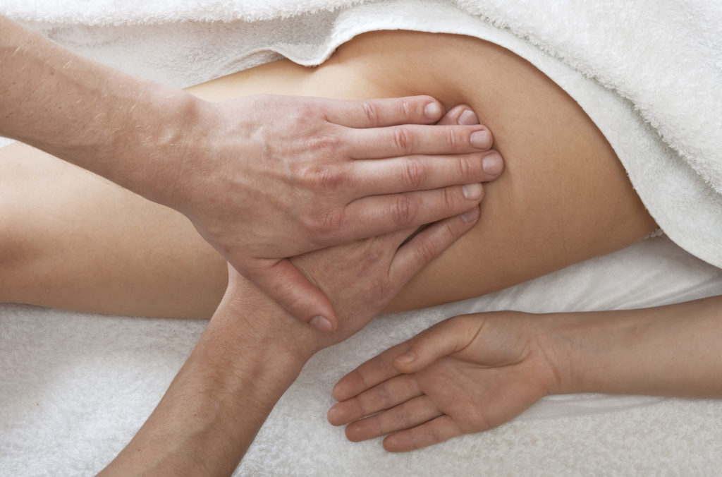 Massager's hands working with a woman's leg. Practice of reflexotherapy.
